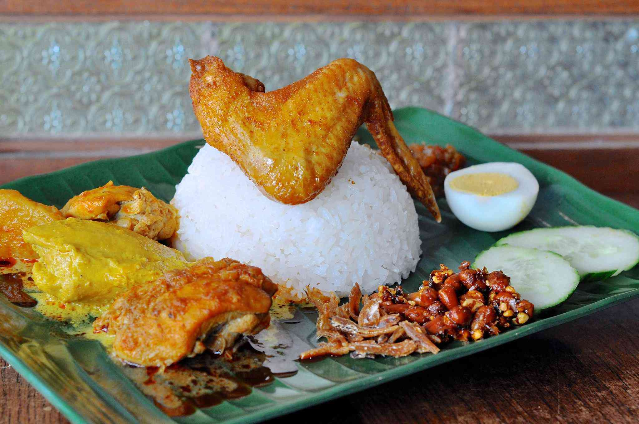Nasi Lemak with one chicken wing on a half-dome of rice