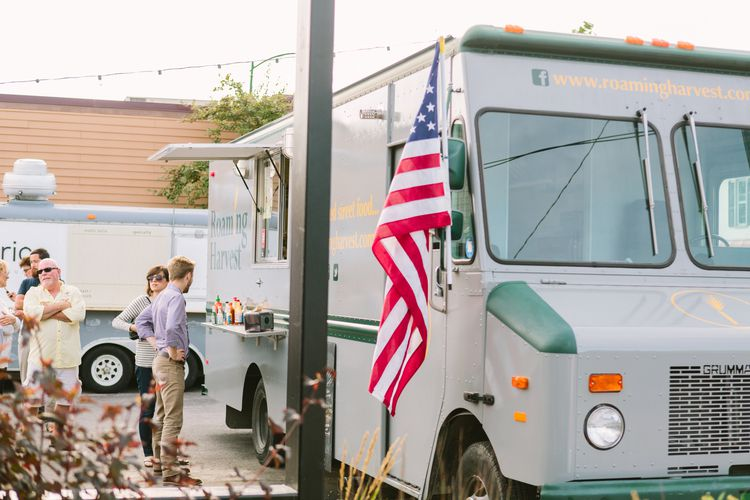 People waiting in line in front of a gray food truck at The Little Fleet in Traverse City, Michigan