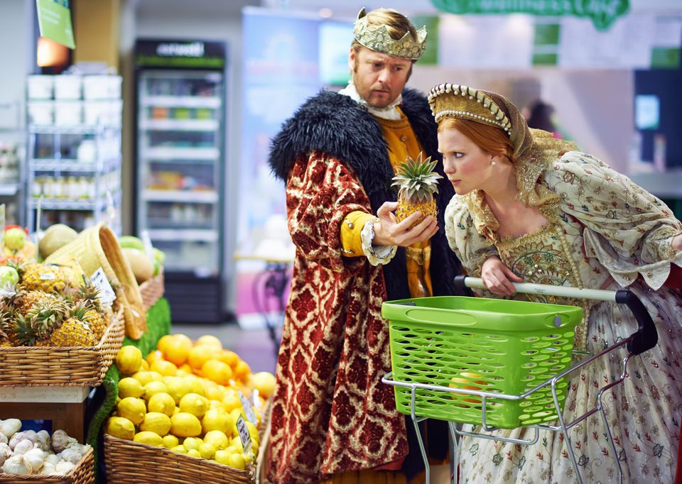 a man and woman dressed as a king and queen in a supermarket