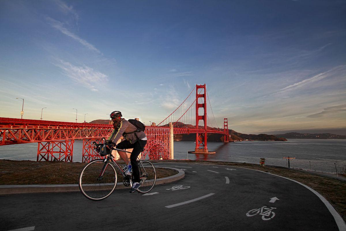 A cyclist pedals past the Golden Gate Bridge