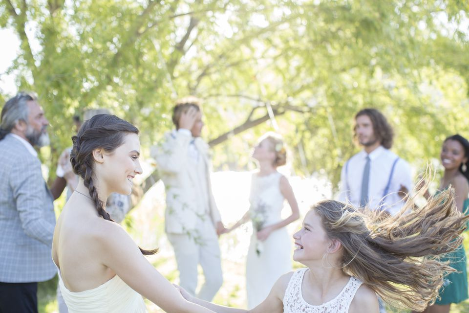 Bridesmaid and girl dancing during wedding reception in domestic garden