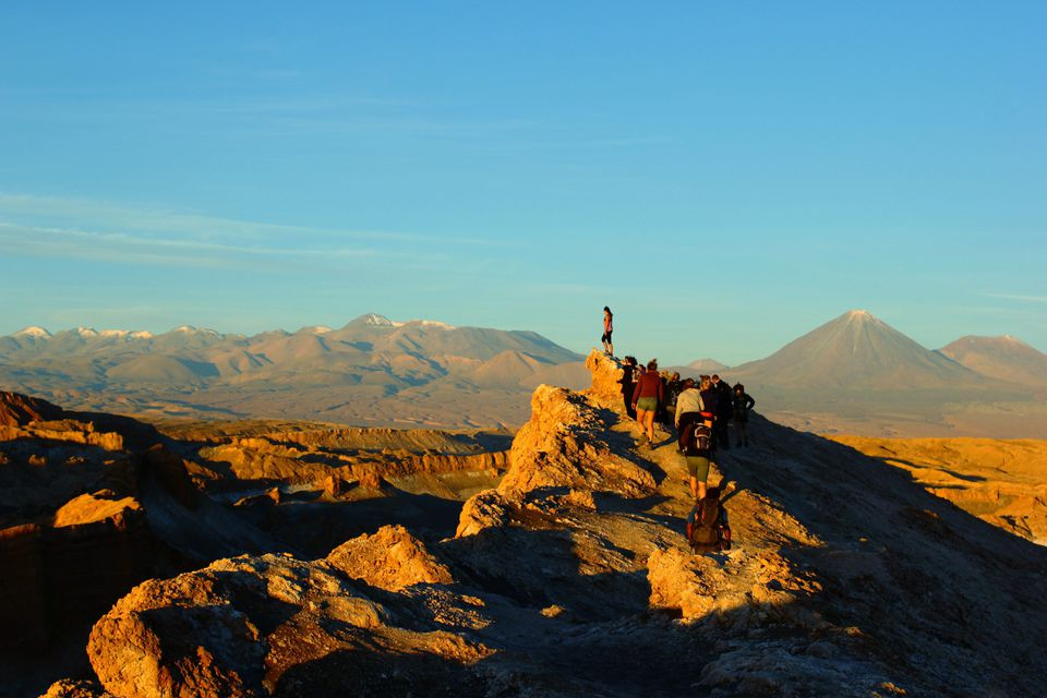 People hiking to the peak of a mountain for a view of the Atacama Desert