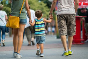 rear view family walking together on summer day in amusement park