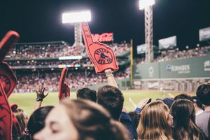 A picture of Fenway Park in Boston taken from the stands showing a Boston Red Sox foam finger in the air