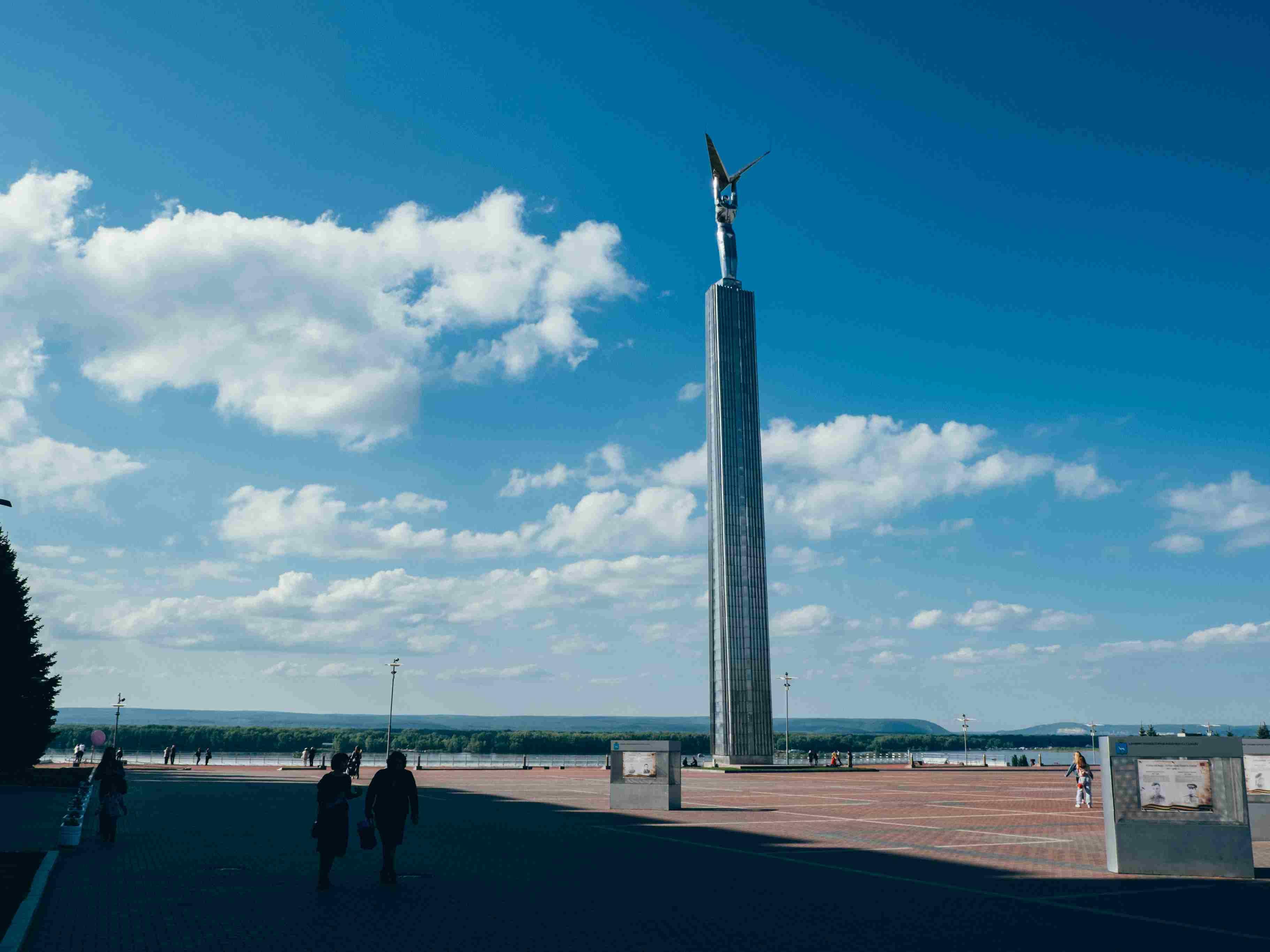 Gente frente a la escultura contra el cielo