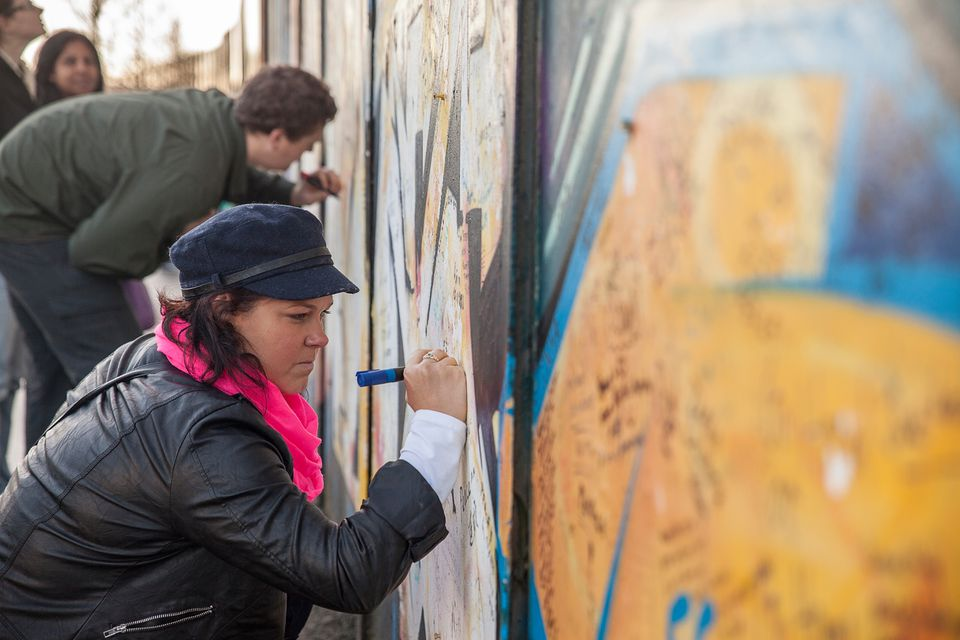 A young woman and a young man write messages on a colorful wall.