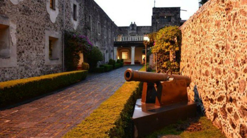 old cannon along a stone wall with a large stone building in the background