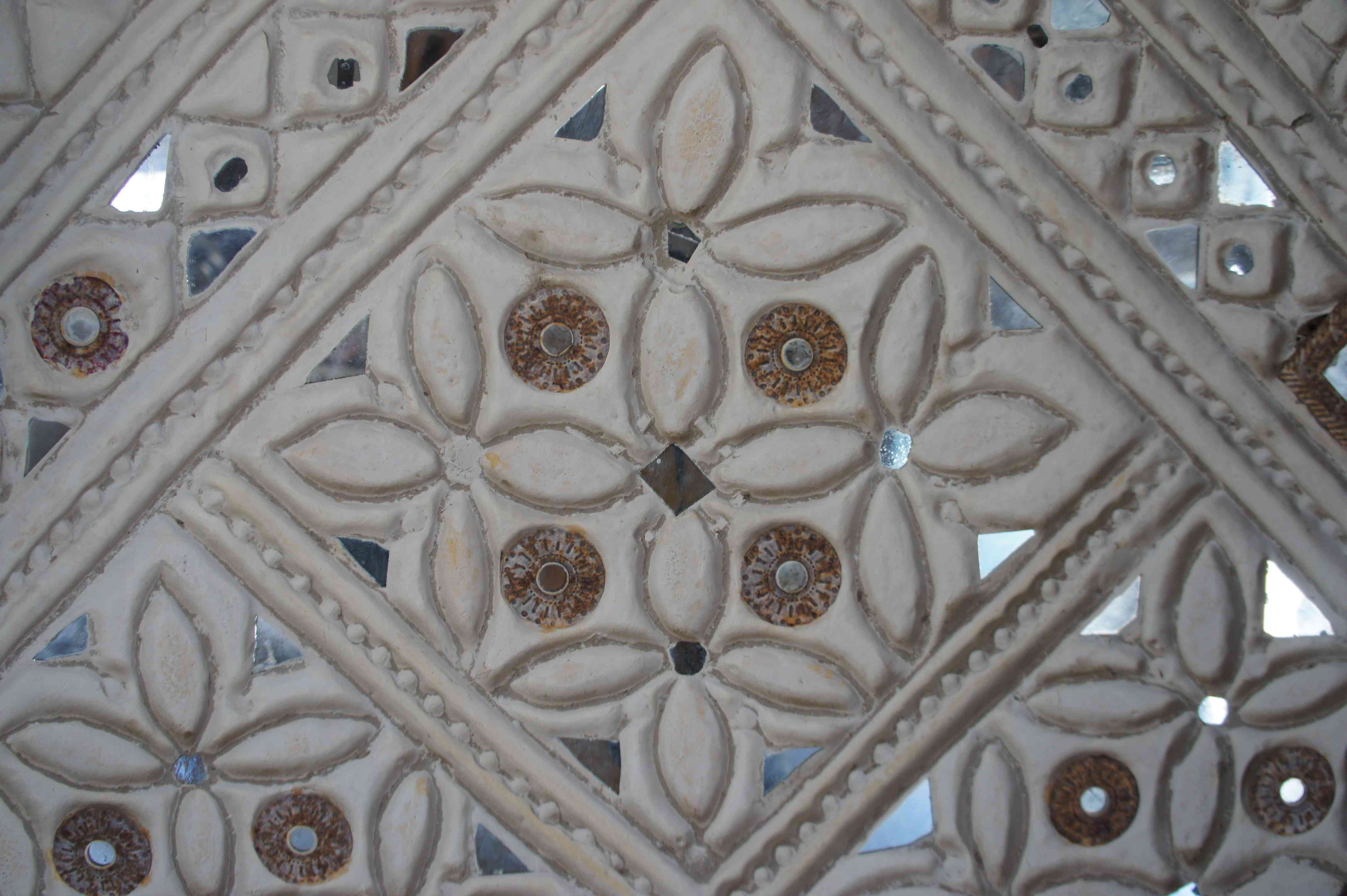 Close up of a mirror work wall design with a floral motif in Kutch india