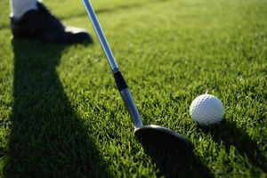 Golfer about to hit ball with wedge, low section (focus on ball)