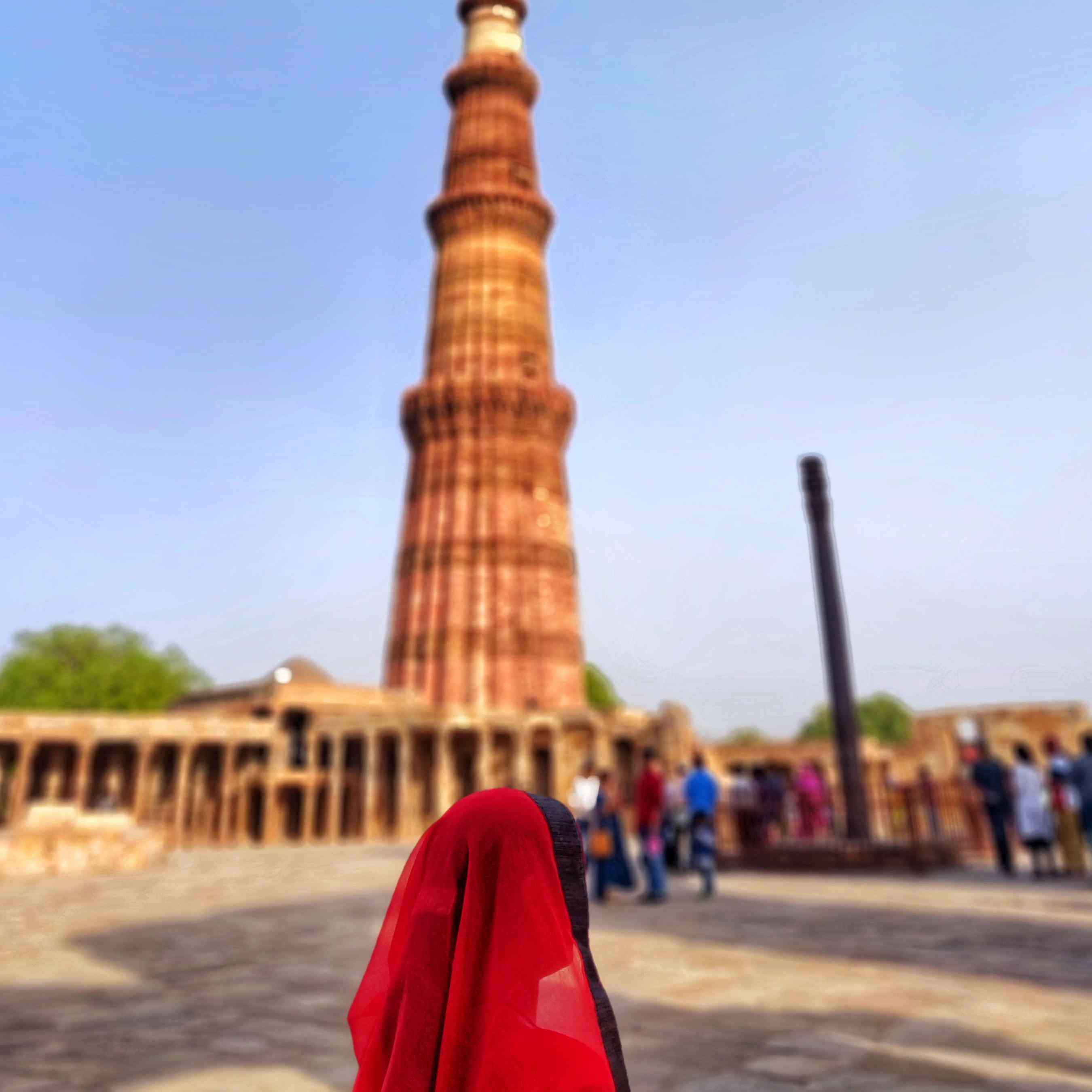 A woman in a red headscarf standing in front of the Qutab Minar