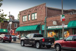 Storefront of Amighetti's on the Hill, St. Louis, MO. Brick storefronts with green awnings and retro signage and neighborhood markers.