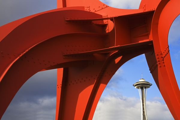 View of the Seattle Space Needle through a large, red, metal sculpture