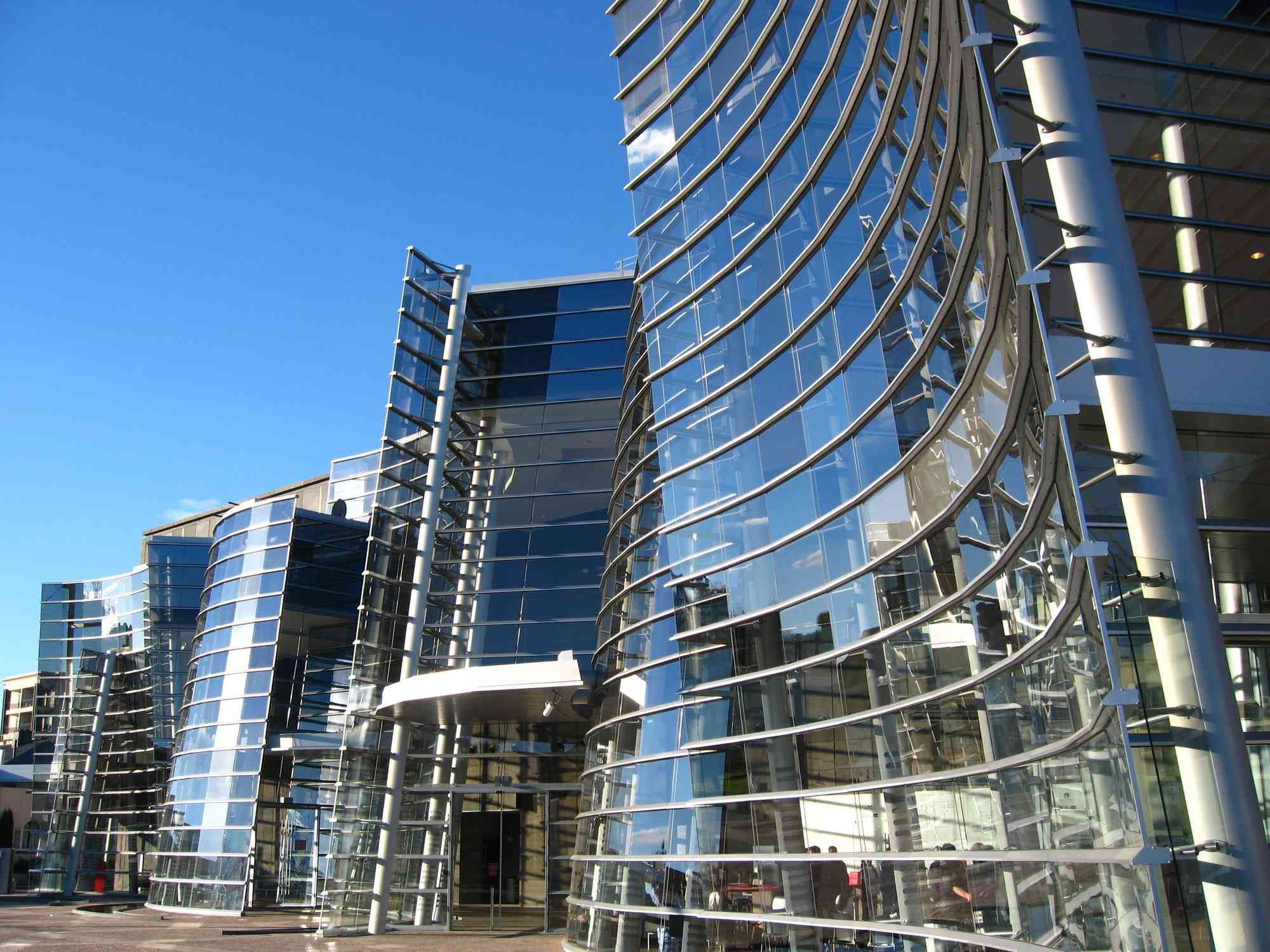 curved glass building with blue sky