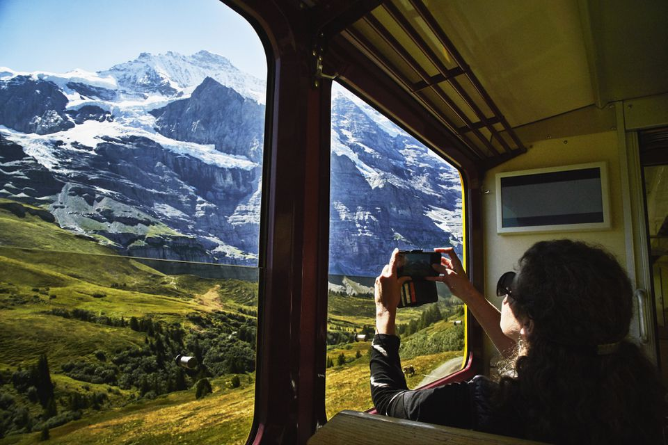 Woman taking photo with smartphone of Jungfrau while riding in train
