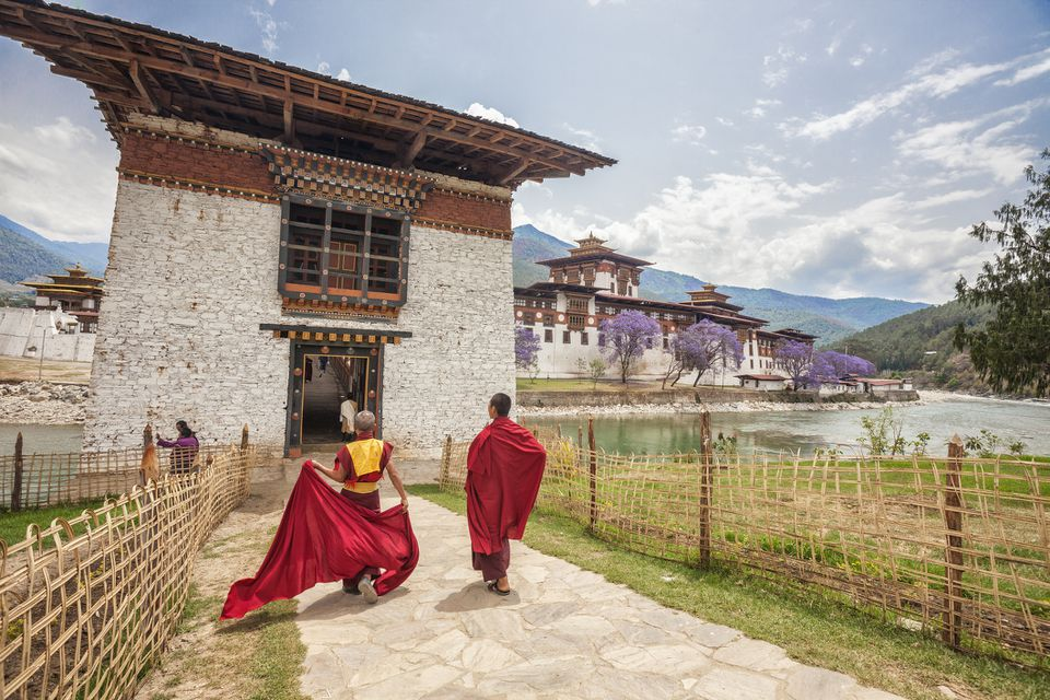 Two monks dressed in traditional red access the Punakha Dzong a former monastery in the town of Punakha