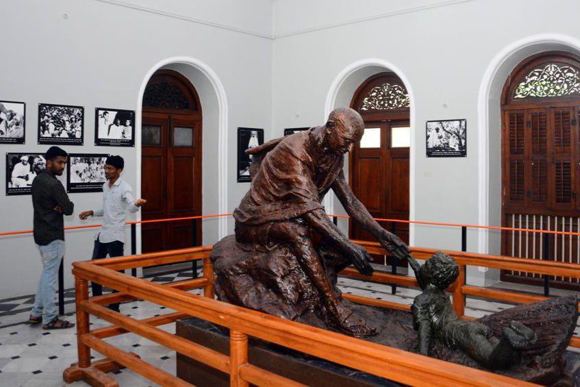 People look at paintings on Mahatma Gandhi at Aga Khan Palace.