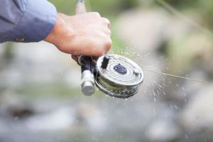 Fishermans hand holding fishing rod with spinning reel