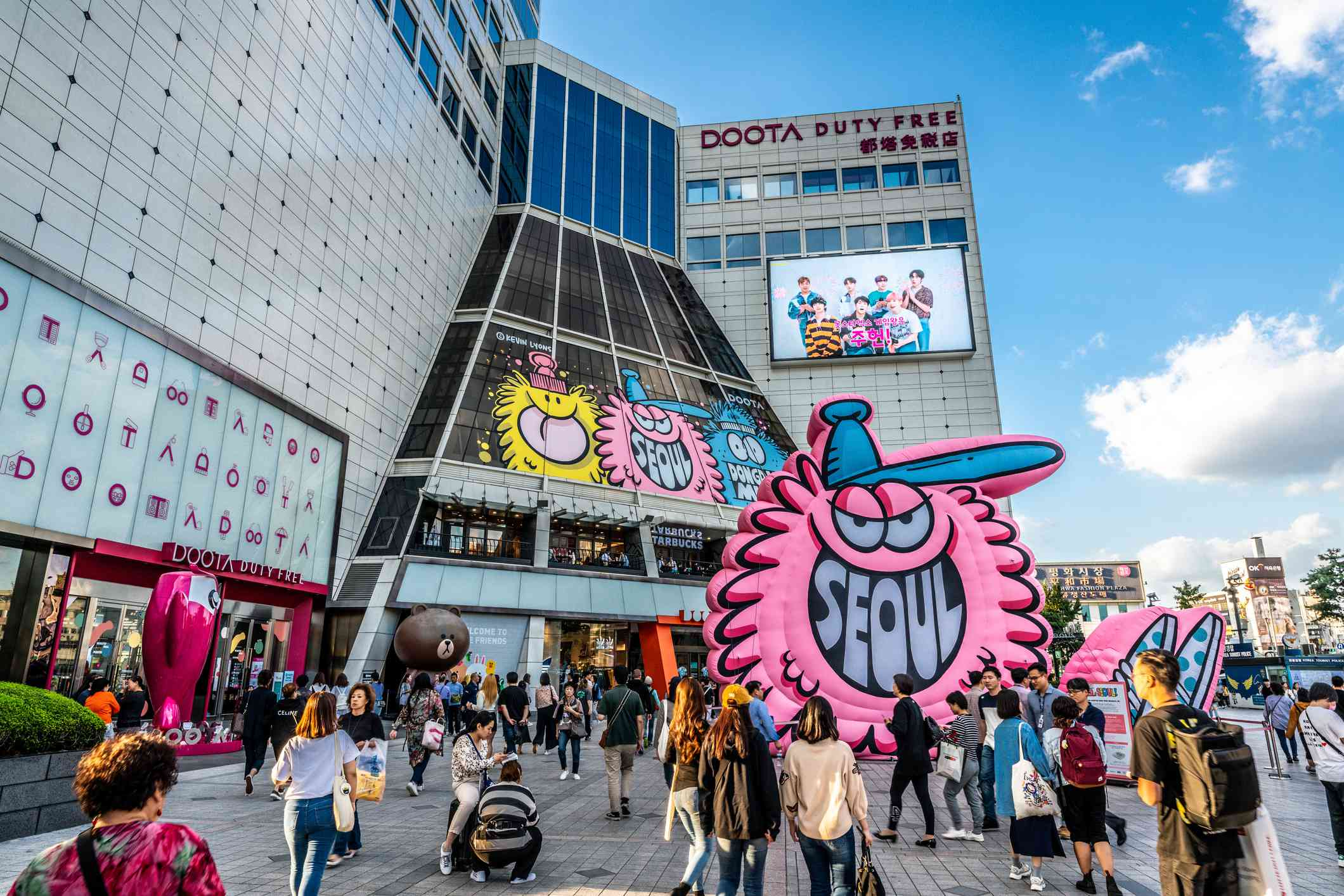 Doota shopping mall exterior view with people and Seoul city sign in Dongdaemun market Seoul South Korea