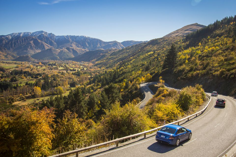 blue car drives down winding road with trees and mountains in the background