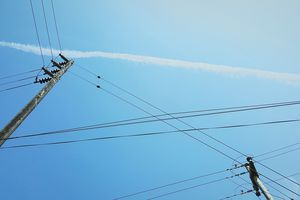 Low Angle View Of Power Lines Against Blue Sky