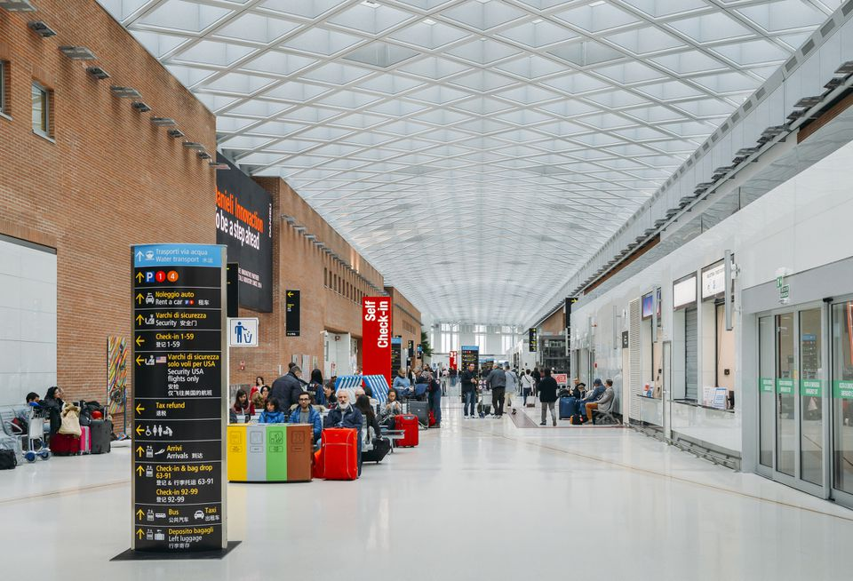 Passengers at the modern interior of Marco Polo International Airport in Venice