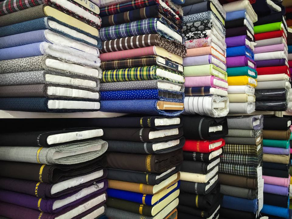 Bolts of fabric stacked in a store.