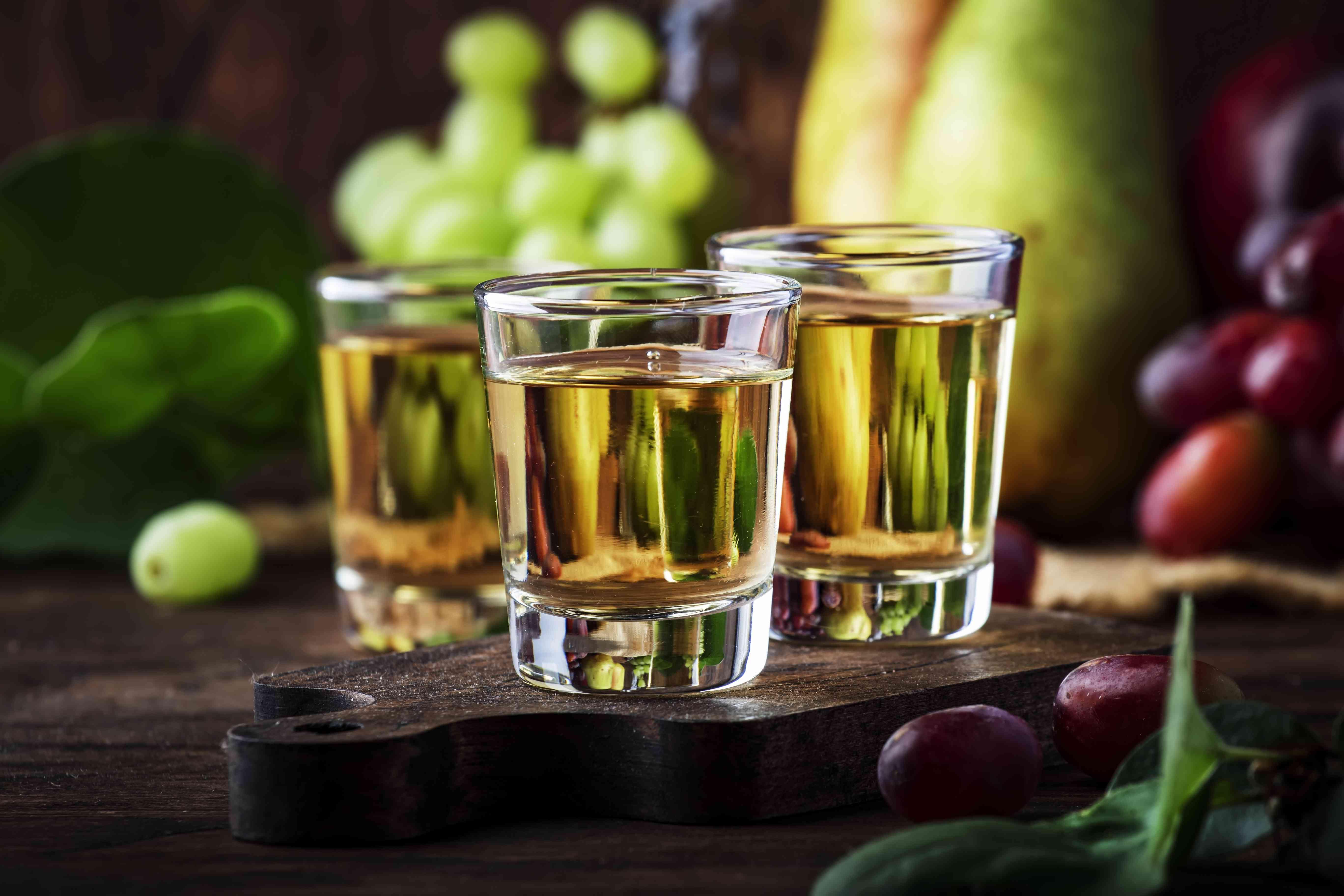 Rakija, raki or rakia - Balkan hard alcoholic drink or brandy from fermented fruits, old wooden table, still life, copy space