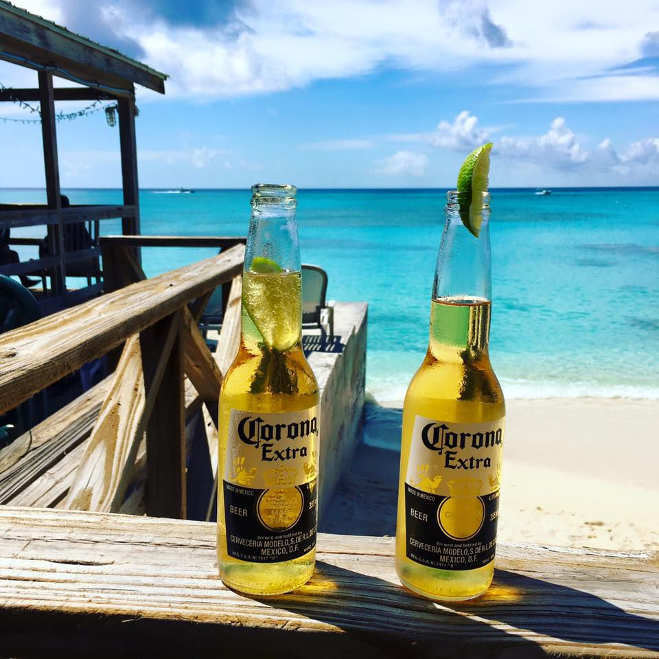 two bottles of corona beer on a wooden railing overlooking a beach