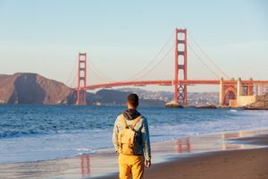 Tourist with backpack looking at Golden Gate Bridge, San Francisco, California, USA