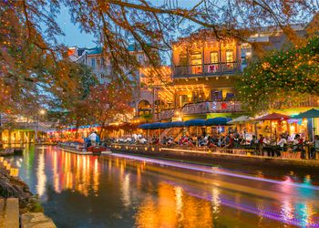 The San Antonio River Walk with people eating on the river front and christmas lights in the trees.