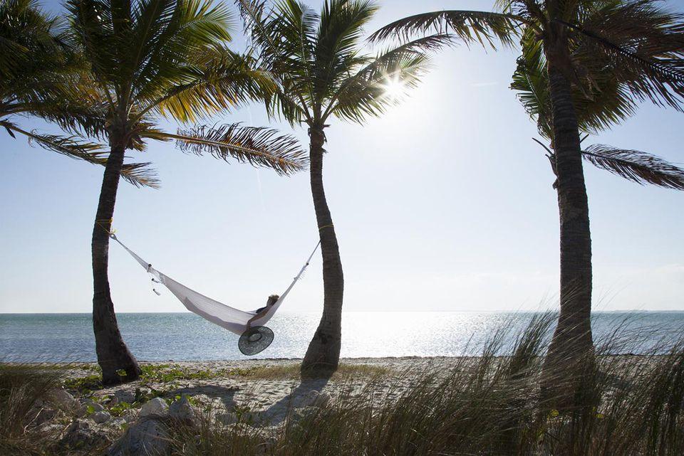Mujer relajándose en una hamaca en la playa