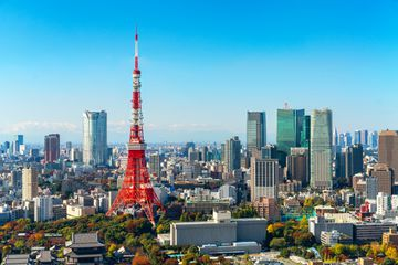 View of the red and white tokyo tower in the business district, photographed from a distance on a cloudless day
