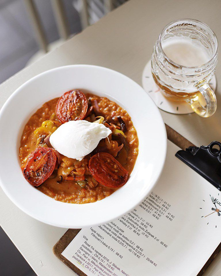 gumbor with three tomato halves and a poached egg on top, on a table with a clipboard menu and a partially-drunk stein of beer