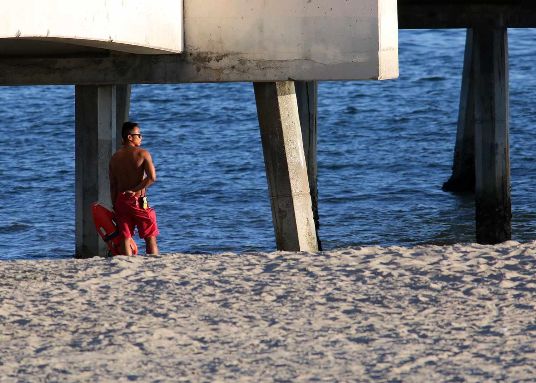 Lifeguard standing under Belmont Pier, Long Beach, California, United States.