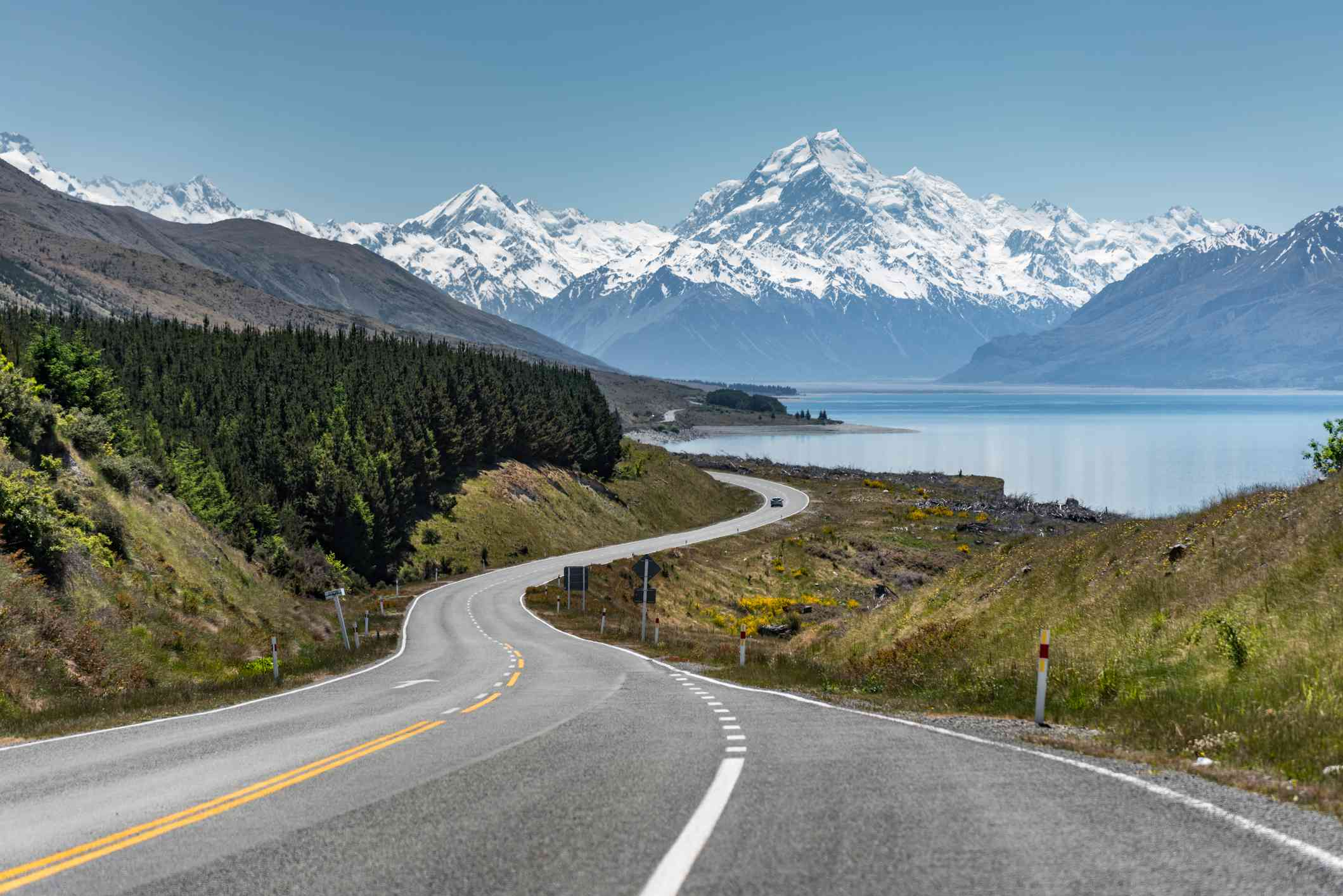 winding road leading to a lake and snowcapped mount cook