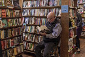 A man reading a book inside City lights books
