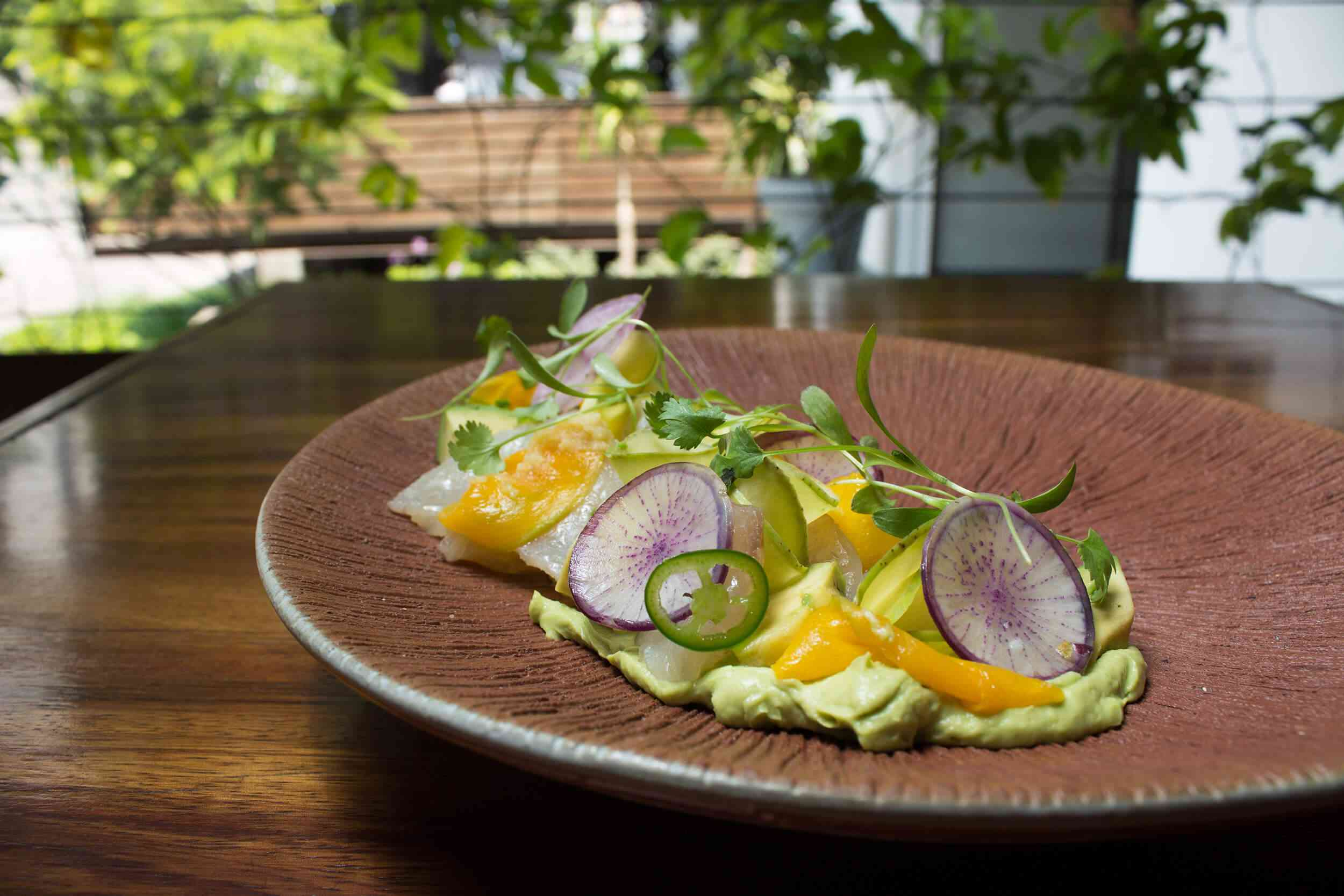 sprouts and sliced vegetables on a brown plate at Allium Guadalajara