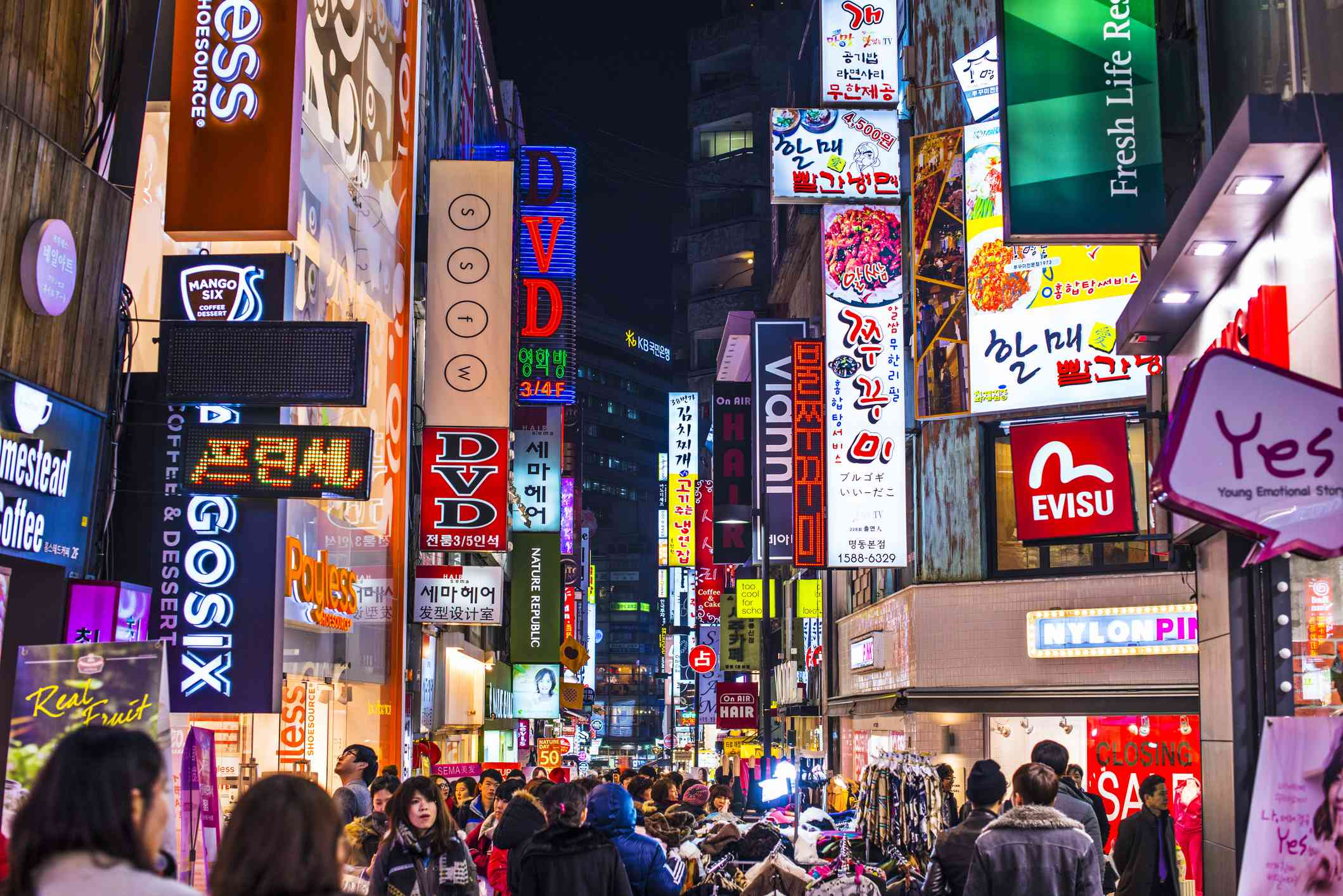 corwd of people walking on a street in seoul at night with colorful signs