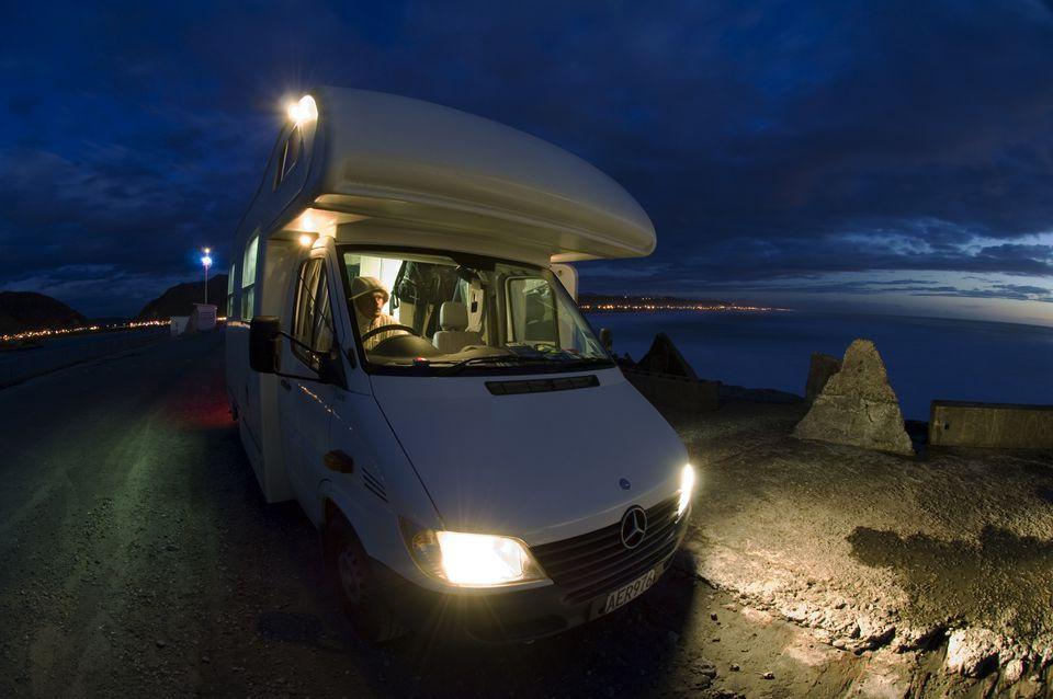 Man in campervan parked at pier at dusk.