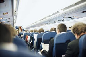 Airplane aisle with group of passengers in seats
