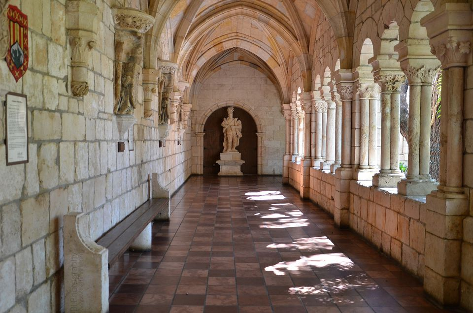 Marble floors, walls, and pillars in hallway leading to statue at Spanish monastery in Miami