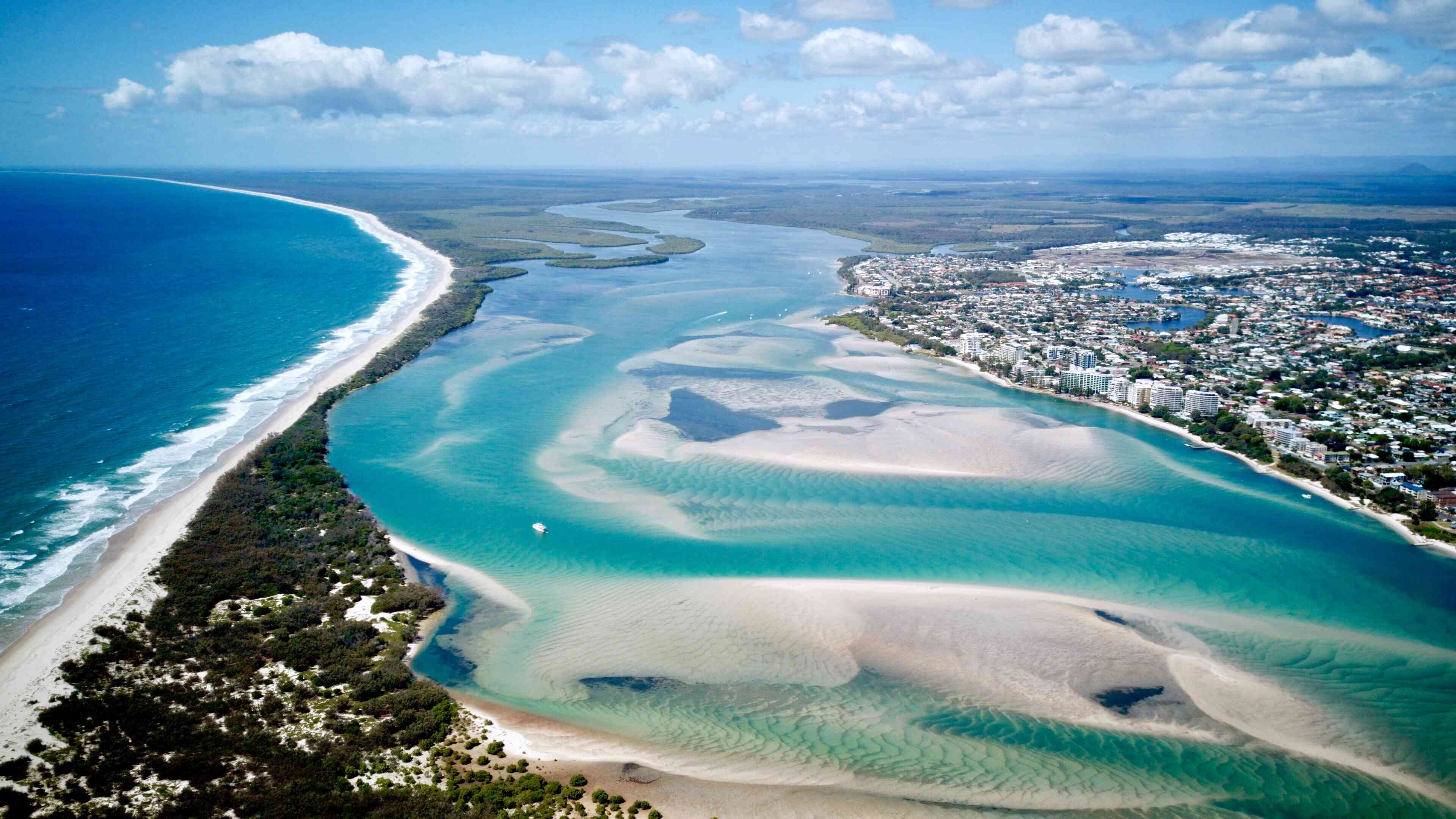 Aerial view of beach and estuary with the city of Caloundra on the right