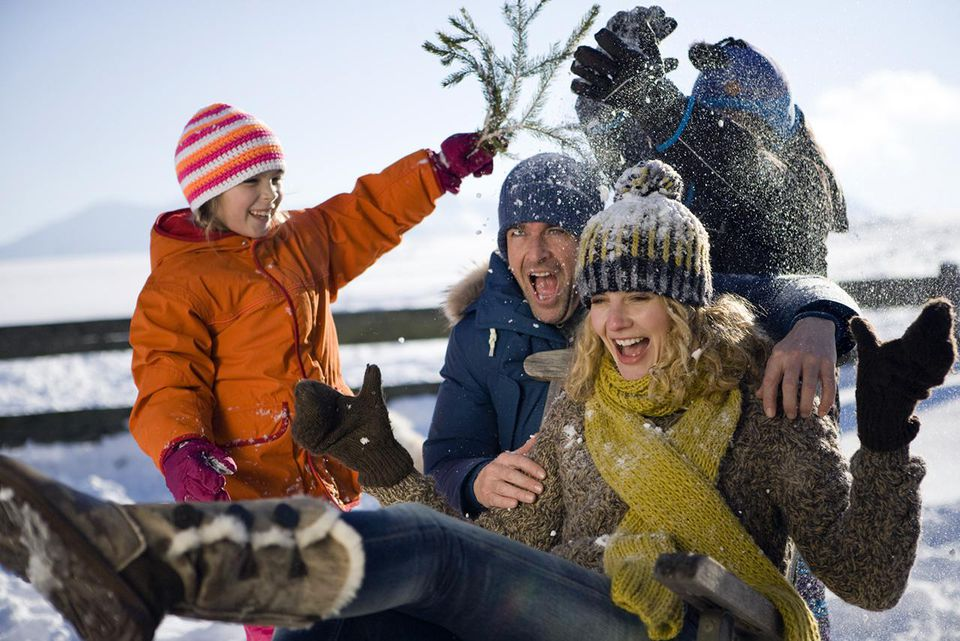 Son and daughter putting snow onto man and woman