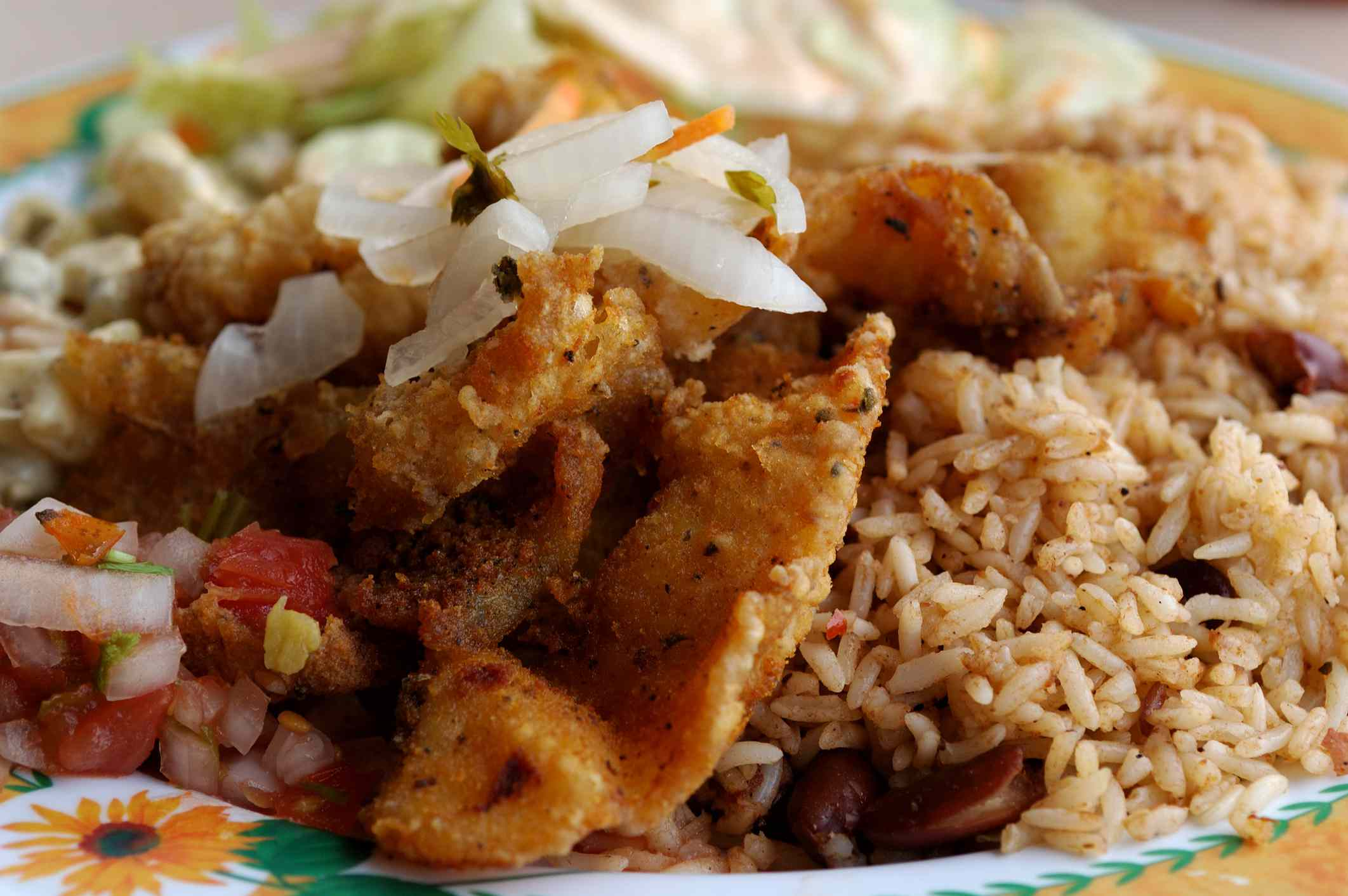 Rice and beans with fried fish fillets and salsa salad