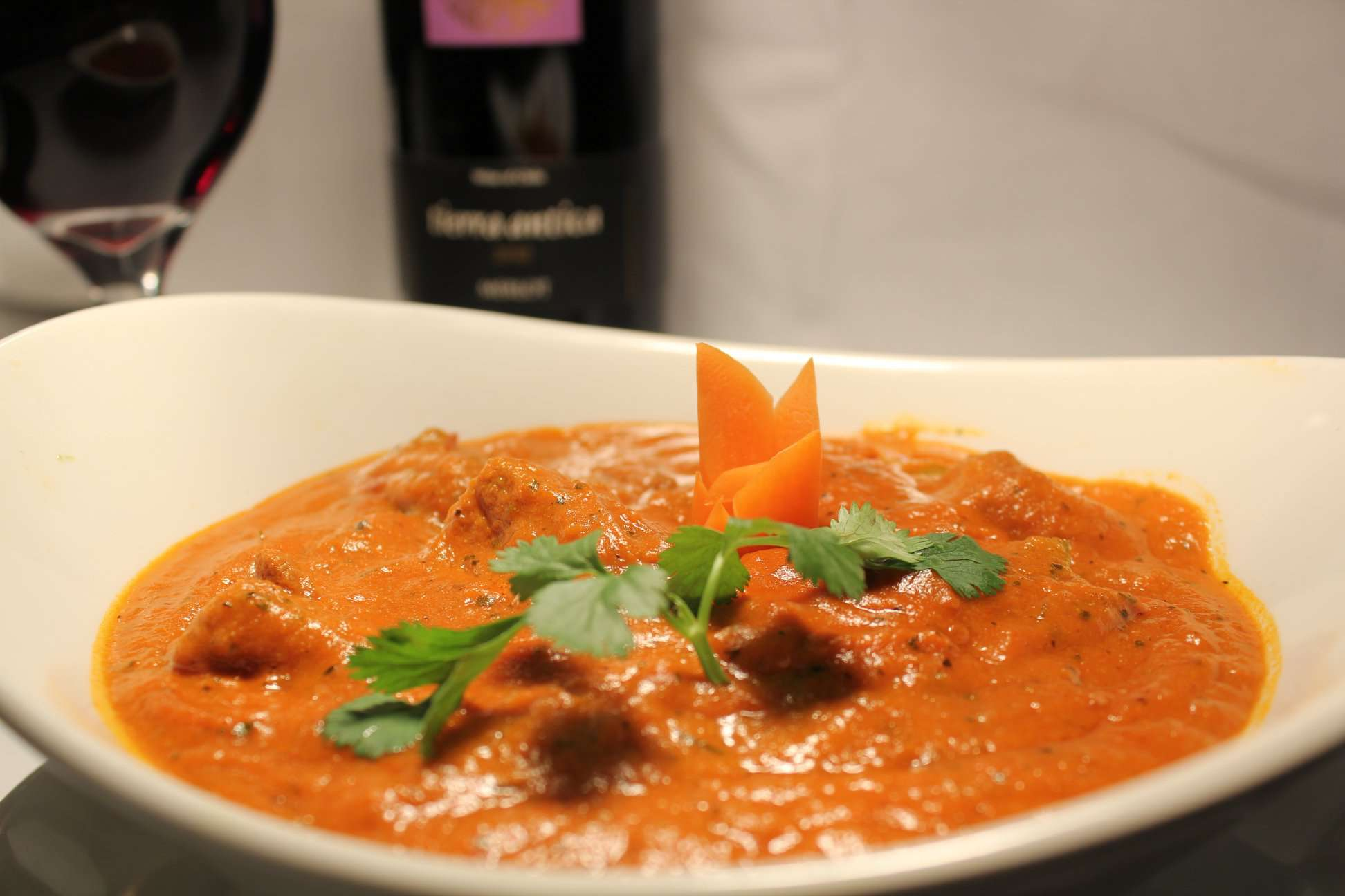 Red curry in a white boy with a sprig of fresh coriander