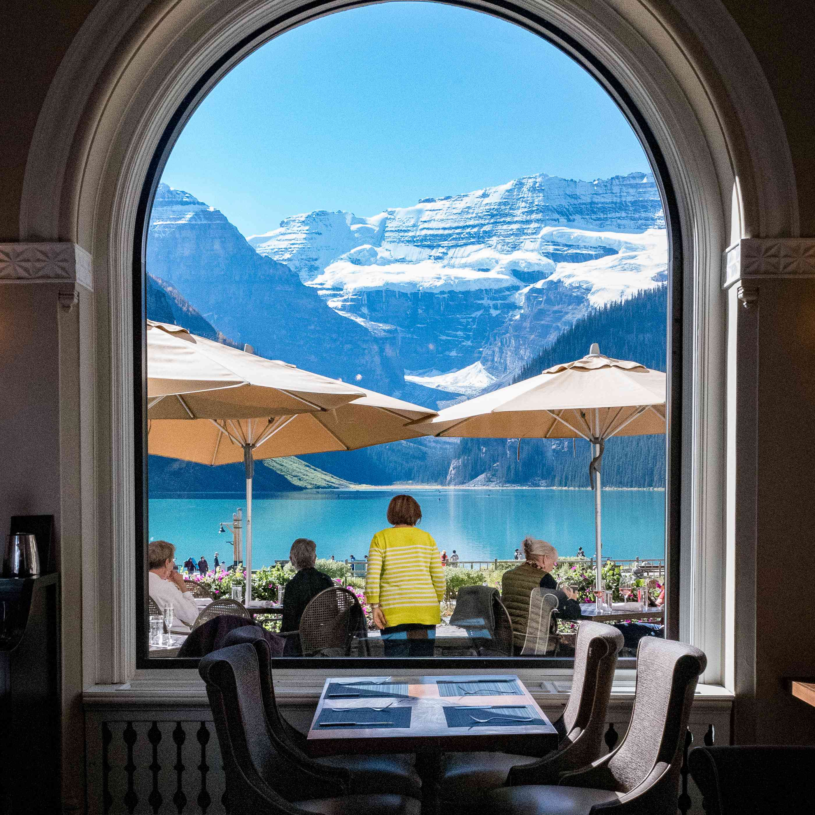 A window looking out to a gorgeous mountain and lake view