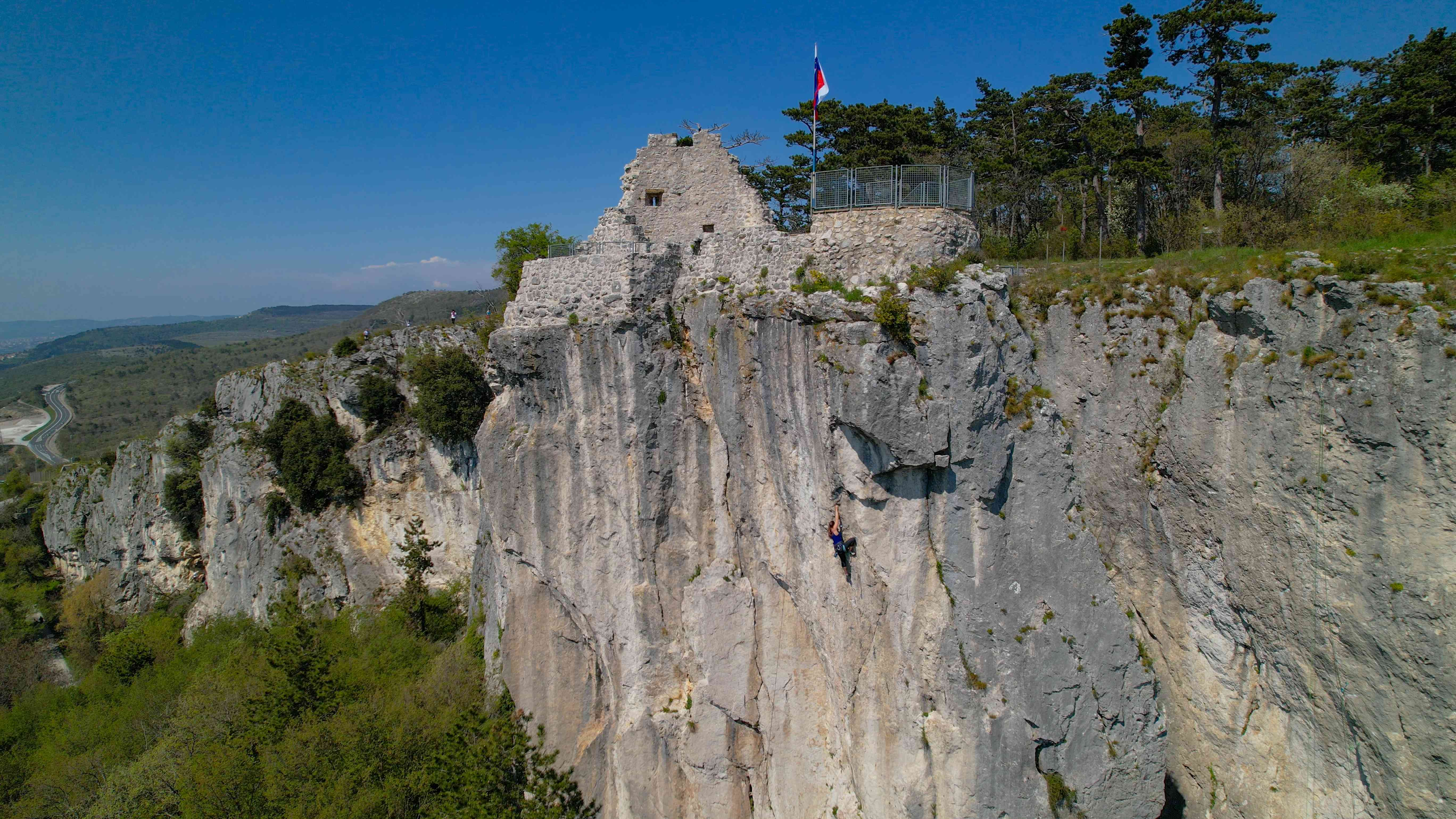 AERIAL: Drone point of view of a female rock climber training in sunny Osp.