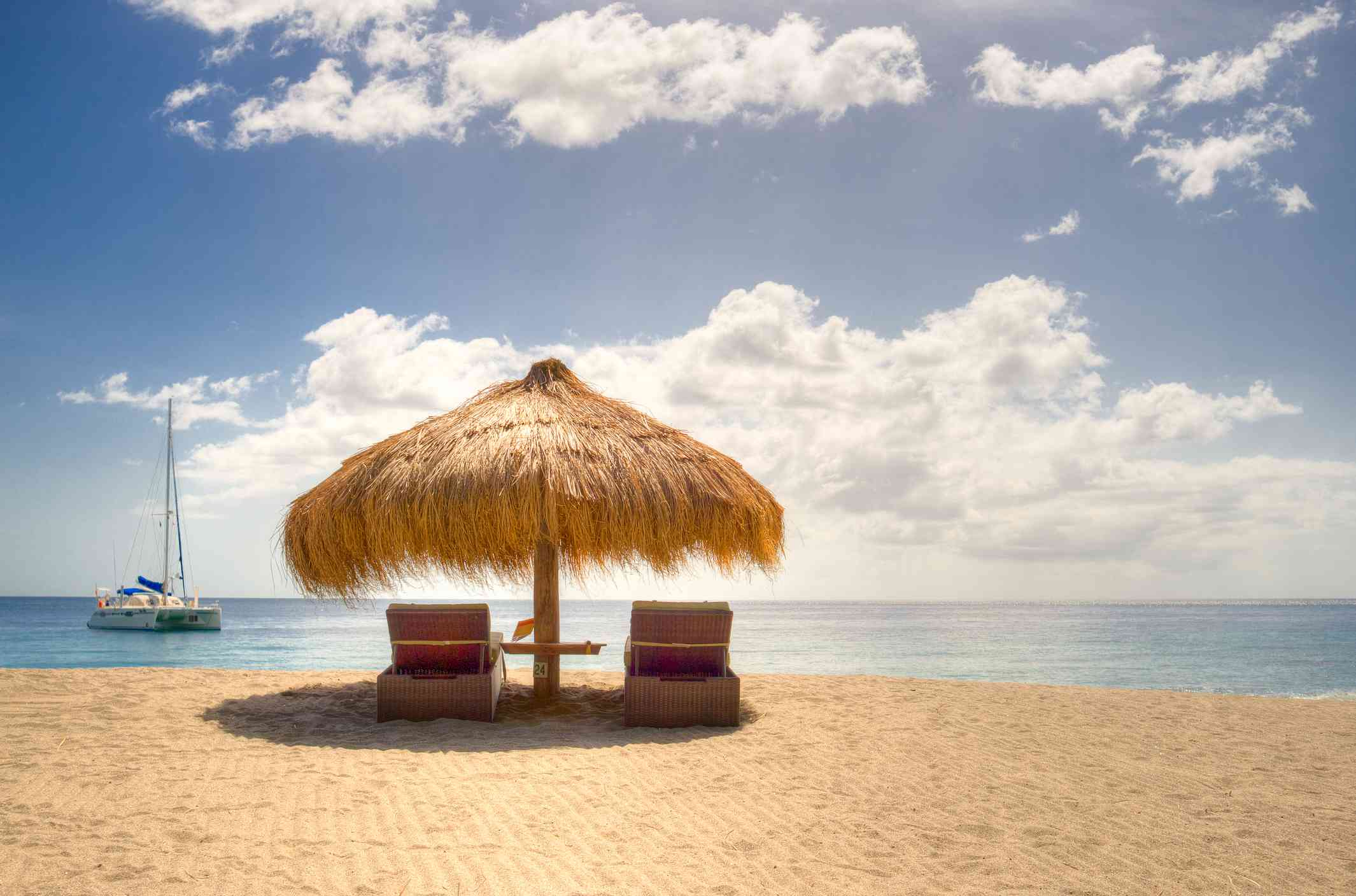 View of umbrella covering two lounge chairs on Anse Chastanet beach