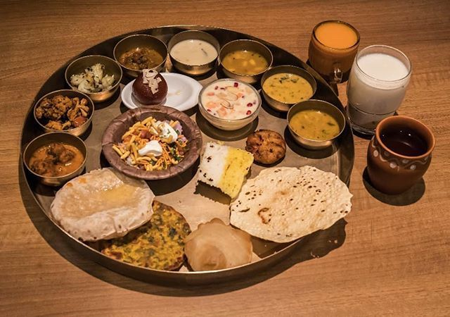 Round tray with a variety of small Indian dishes