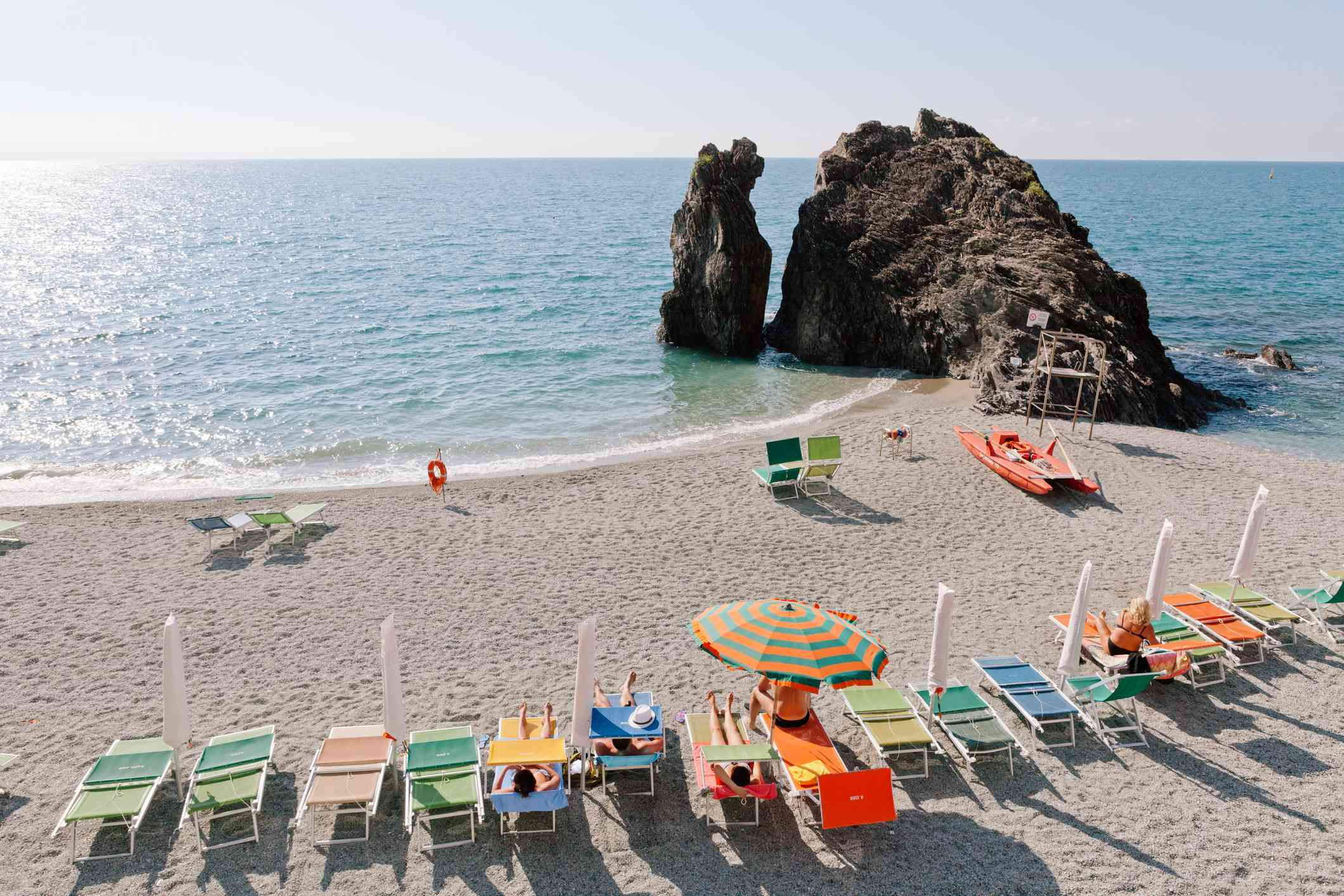 Umbrellas and lounge chairs, plus a rock formation on Monterosso al Mare beach